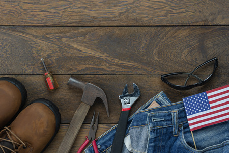 Table top view aerial image of decoration the sign of USA labor day on Sep 3,2018 background concept. Flat lay accessories tools and clothing  for worker on modern rustic brown wooden with copy space. Stock Photo