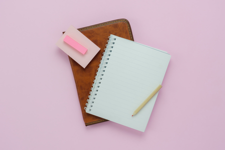 Table top view aerial image of back to school of education season background concept.Flat lay the diary with note nook and pencil on modern rustic pink paper.Free space for creative design mock up.