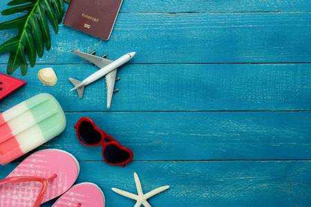 Table top view aerial image of fashion to travel in summer holiday background.Flat lay accessories clothing for traveler.Passport & sunglasses with airplane on modern  blue wooden.Space for content.