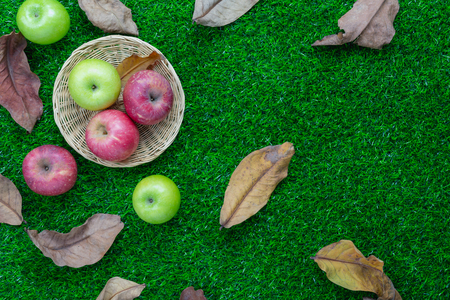 Table top view aerial image of decoration Fall harvest or Rosh Hashanah day background concept.Flat lay apple in basket with dry leaf all objects on modern rustic green grass.Copy space for add text.