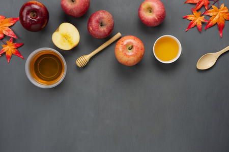 Table top view aerial image of decorations Jewish holiday Rosh Hashana background concept.Flat lay of variety apple & honey with maple leaf on modern rustic grey wood.Free space for design text. Stock Photo