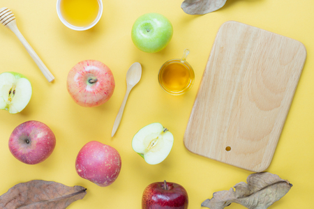 Table top view aerial image of decorations Jewish holiday Rosh Hashana background concept.Flat lay of variety apple & honey bee with wood plank on modern rustic yellow paper.Free space for creative. Stock Photo