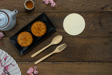 Table top view aerial image of decoration Chinese Moon Festival background concept.Flat lay cake & tea and pink blossom on modern rustic brown wooden wallpaper.Free space for creative design mock up