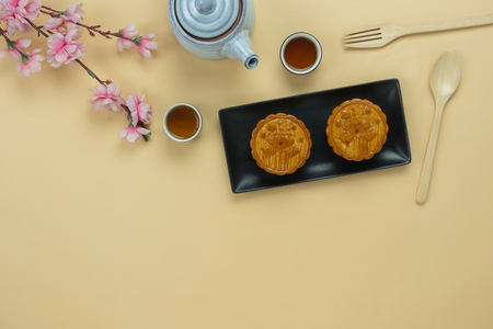 Table top view aerial image of decorations Chinese Moon Festival background concept.Flat lay cake & tea and pink blossom on modern rustic yellow paper wallpaper.Free space for creative design mock up Stock Photo