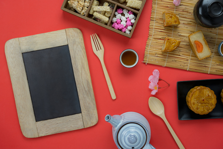 Table top view aerial image of decoration Chinese Moon Festival background concept.Flat lay Chinese food cake & tea and pink blossom on modern rustic red paper wallpaper.Blackboard for design mock up