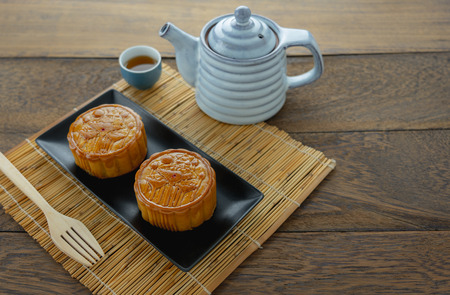 Close up image of food dessert decorations Chinese Moon Festival background concept.Accessories cake & tea cup and bamboo on modern rustic wooden plank.Free space for creative design mock up.