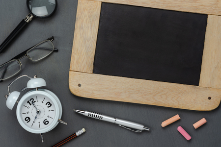Table top view aerial image of back to school of education season background concept.Flat lay accessories blackboard with clock on modern rustic grey wooden.Free space for creative design mock up.