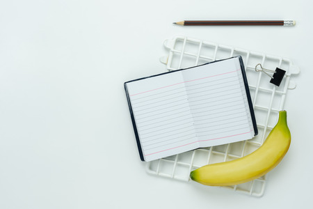 Table top view aerial image of back to school of education season background or diet healthcare concept.Flat lay note nook with banana and objects on modern rustic white wooden.Copy for creative text.