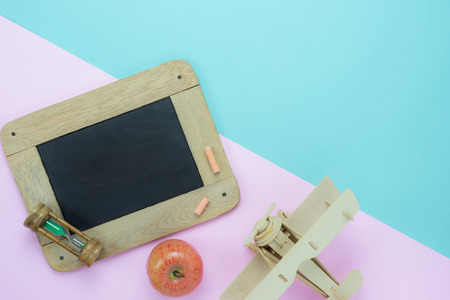 Table top view aerial image of back to school of education season background concept.Flat lay blackboard & accessories objects on modern rustic blue & pink paper.Free space for creative design.