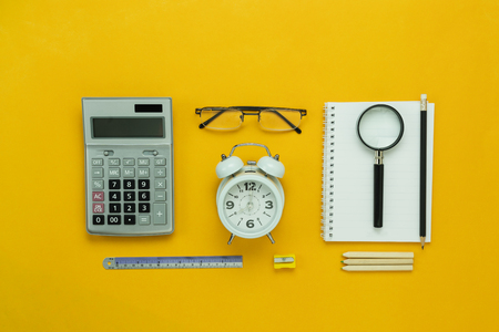 Table top view aerial image of back to school of education season background concept.Flat lay accessories for business finance the clock & calculator and objects on modern rustic yellow paper. Stock Photo