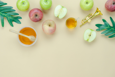 Table top view aerial image of decorations Jewish holiday the Rosh Hashana background concept.Flat lay of variety apple & honey bee and green left on modern rustic yellow paper.Free space for design. Stock Photo