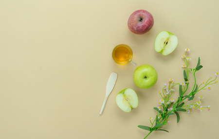 Table top view aerial image of decorations Jewish holiday the Rosh Hashana background concept.Flat lay of variety apple & honey bee and flower on modern rustic yellow paper.Free space for design.