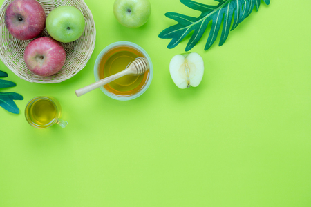 Table top view aerial image of decorations Jewish holiday the Rosh Hashana background concept.Flat lay of variety apple & honey bee and green left on modern rustic green paper.Free space for design.
