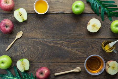 Table top view aerial image of decorations Jewish holiday the Rosh Hashana background concept.Flat lay of variety apple & honey bee on modern rustic brown wooden.Free space for creative mock up.