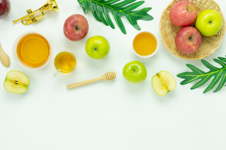 Table top view aerial image of decorations Jewish holiday the Rosh Hashana background concept.Flat lay of variety apple & honey bee on modern rustic white wooden.Free space for creative mock up. Stock Photo