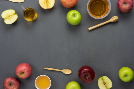 Table top view aerial image of decorations Jewish holiday the Rosh Hashana background concept.Flat lay of variety apple & honey bee on modern rustic black wooden.Free space for creative mock up. Stock Photo