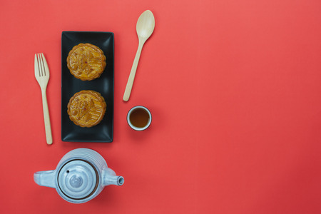 Table top view aerial image of decorations Chinese Moon Festival background concept.Flat lay sweet moon cake & cup tea on modern rustic red paper wallpaper.Free space for creative design mock up.