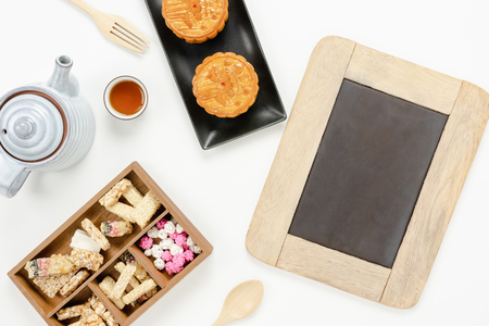 Table top view aerial image of decorations Chinese Moon Festival background concept.Flat lay snack break the sweet cake & tea with backboard for mock up on modern rustic white wooden wallpaper.
