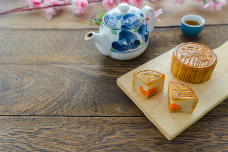 Close up image of food dessert decorations Chinese Moon Festival background concept.Food & drink the cake with tea cup and pink blossom on modern rustic wooden plank.Free space for design add text. Stock Photo