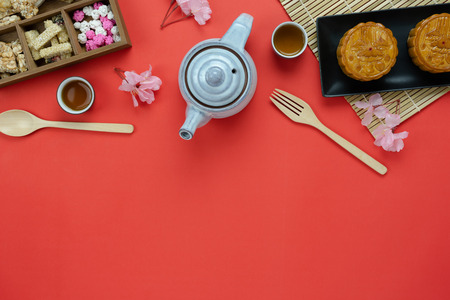 Table top view aerial image of decorations Chinese Moon Festival background concept.Flat lay meal set of coffee break the sweet cake & tea pot with snack on red paper backdrop.creative design mock up