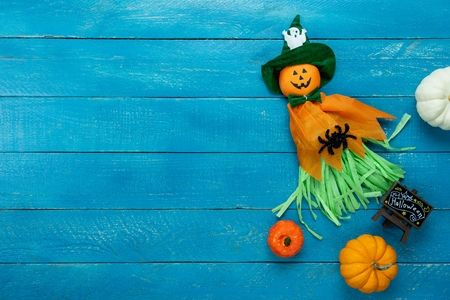 Table top view aerial image of decoration Happy Halloween day background concept.Flat lay accessories essential object to party the pumpkin doll & sweet candy on blue wooden.Space for creative design.