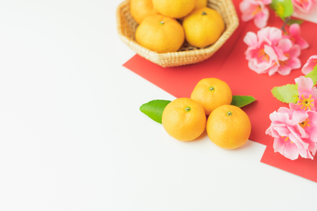 Top view aerial image shot of arrangement decoration Chinese new year & lunar new year holiday background concept.Flat lay fresh orange with pink cheery blossom & red pocket money on  white wooden.