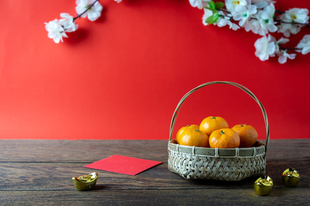 Accessories on Lunar New Year & Chinese New Year vacation concept background.Orange in wood basket with  red pocket money and flower on modern rustic brown & red backdrop at home office desk studio. Stock Photo