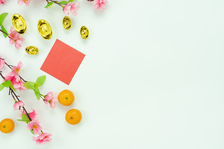 Chinese language mean rich or wealthy and happy.Top view decoration Chinese new year & lunar new year holiday background concept.Flat lay orange with pink flower on white wooden at home office desk.