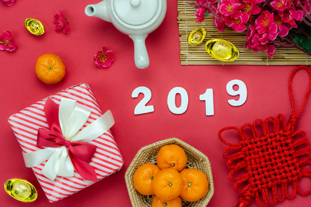 Chinese language mean rich or wealthy and happy.Table top view Lunar New Year & Chinese New Year vacation concept background.Flat lay food & dink the orange with gift box and flower on red paper