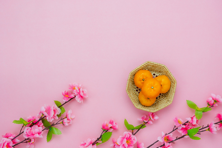 Chinese language mean rich or wealthy and happy.Table top view Lunar New Year & Chinese New Year vacation concept background.Flat lay orange in basket and cherry blossom on pink paper and copy space. 版權商用圖片