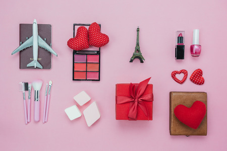 Table top view aerial image of decoration valentine's day background concept.Flat lay essential items red heart & gift box on modern pink paper with clothing women & cosmetic for travel Paris France. Standard-Bild