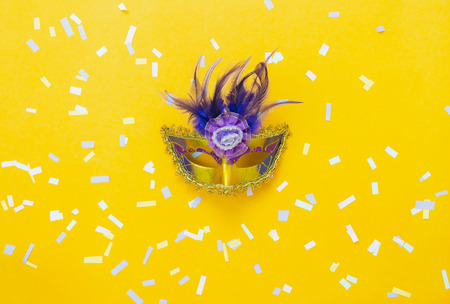 Table top view aerial image of beautiful colorful carnival season or photo booth prop Mardi Gras background.Flat lay object close up gold mask & confetti on yellow wallpaper.Space for text mock up. Stock Photo