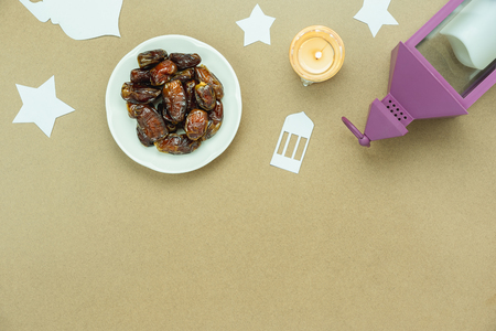Table top view aerial image of decoration Ramadan Kareem holiday background.Flat lay date in plate with dome paper & lighting with star on modern rustic brown wood at office desk.Space for mock up. Stock Photo