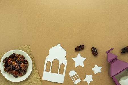 Table top view aerial image of decoration Ramadan Kareem holiday background.Flat lay date with rosary & lighting and cup of tea.Essential object on modern rustic brown wooden at office desk.copy space Stock Photo