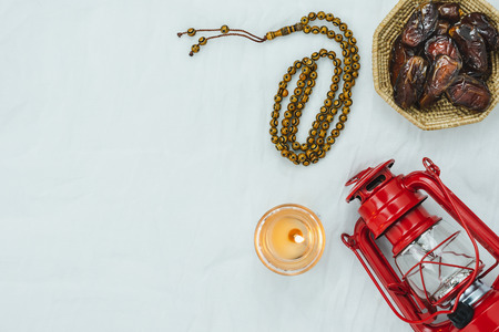 Table top view aerial image of decoration Ramadan Kareem holiday background.Flat lay date with rosary & red lighting.Essential objects on modern rustic white clothing at office desk.copy space