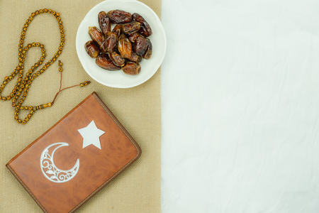 Table top view aerial image of decoration Ramadan Kareem holiday background.Flat lay date in plate with star & moon paper & rosary.Holy Koran on modern rustic white clothing at office desk.