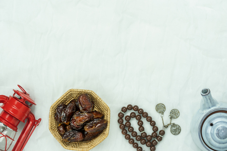 Table top view aerial image of decorations Ramadan Kareem holiday background.Flat lay date with rosary & lighting and cup of tea.Halal meal set for fasting is obligatory for Muslim on white clothing.