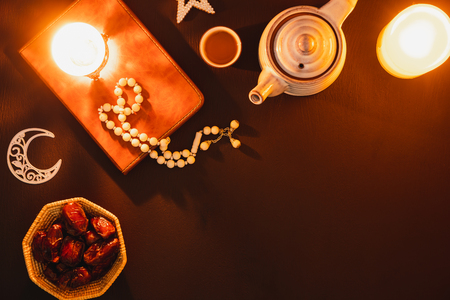 Table top view aerial image of decorations Ramadan Kareem holiday background.Flat lay food & drink of Halal meal set for fasting is obligatory for Muslim on black wooden.Rosary & cup of tea with koran