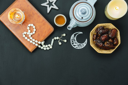 Table top view aerial image of decorations Ramadan Kareem holiday background.Flat lay date with rosary & lighting and cup of tea.Halal meal set for fasting is obligatory for Muslim on black wooden.