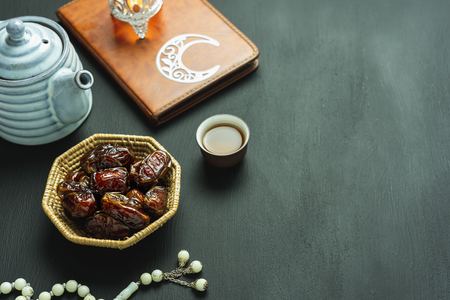 Table top view aerial image of decoration Ramadan Kareem holiday background.Flat lay date with rosary & lighting and cup of tea.Essential objects the holy koran on modern rustic black wooden. Stock Photo