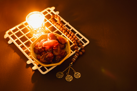 Table top view aerial image of decorations Ramadan Kareem holiday background.Flat lay dates with brown rosary & lighting.Halal meal set for fasting is obligatory for Muslim on black wooden.low key Stock Photo