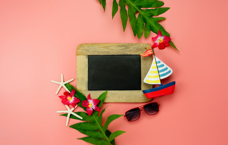 Table top view accessory plan to travel beach in summer holiday background concept.Flat lay  palm leaf with many essential items flower & sunglasses on pink paper.Blackboard for design text