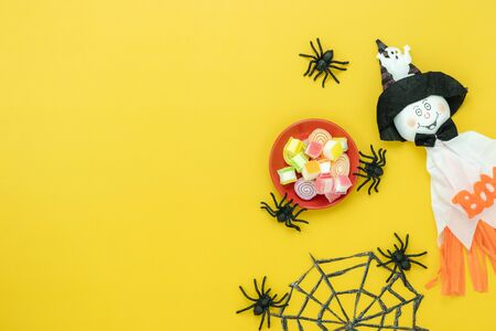 Table top view aerial image of decoration Happy Halloween day background concept.Flat lay accessories essential object to party the pumpkin & doll and hat on white wooden.Space for creative design.