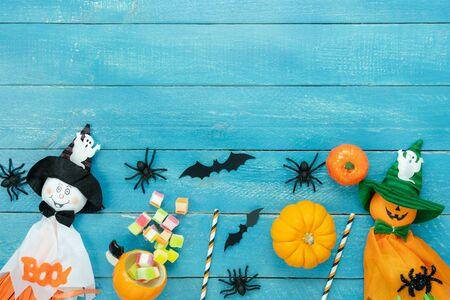 Tischplattenansicht Luftbild der Dekoration Happy Halloween Day Hintergrundkonzept. Flaches Zubehör wesentliches Objekt zum Party der Kürbis & Puppe und Süßigkeiten auf blauem Holz. Platz für kreatives Design.