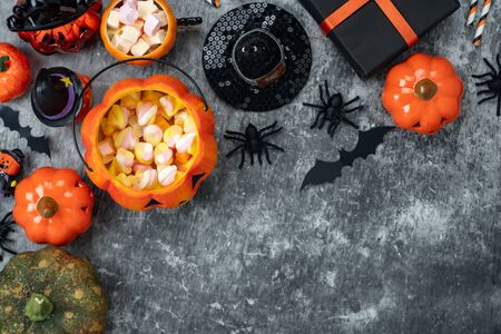 Table top view aerial image of decoration Happy Halloween day background concept.Flat lay accessories essential object to party the pumpkin & sweet candy on rustic stone.Space for creative design.