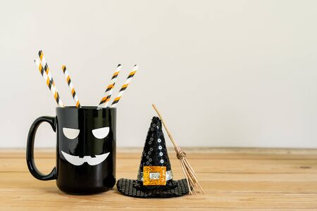 Accessories of decorations Happy Halloween day background concept.Jack O Lanterns cup of drink with Witchs broom of object to party season on modern rustic brown & white stone backdrop.copy space.