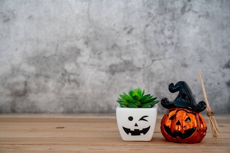 Accessories of decorations Happy Halloween day background concept.Jack O Lanterns cactus with spooky pumpkins object to party season with witchs broom on modern rustic brown & white stone backdrop.