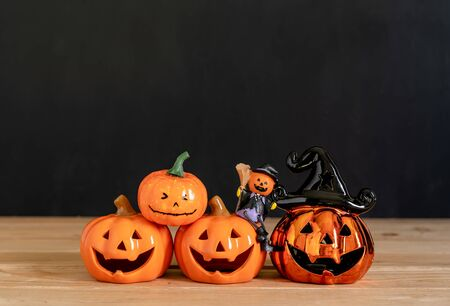 Accessories of decorations Happy Halloween day background concept.Variety of Jack O Lanterns pumpkins object to party season with spider on modern rustic brown & black stone backdrop.copy space.