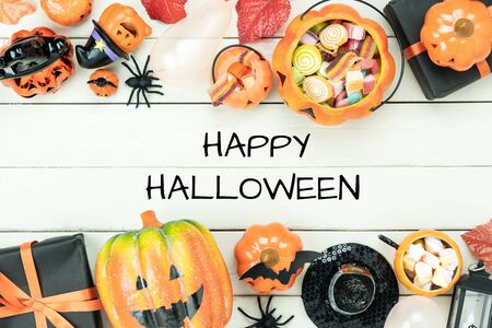 Table top view aerial image of decorations Happy Halloween day background holiday concept.Flat lay objects to party pumpkins and spider with candy sweet on white wooden wallpaper.text design season. Stock Photo