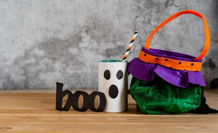 Accessories of decorations Happy Halloween sale day background concept.Cup of drink with pumpkin bag object to party season with spider on  brown & white backdrop at home office desk studio.copy space Stock Photo